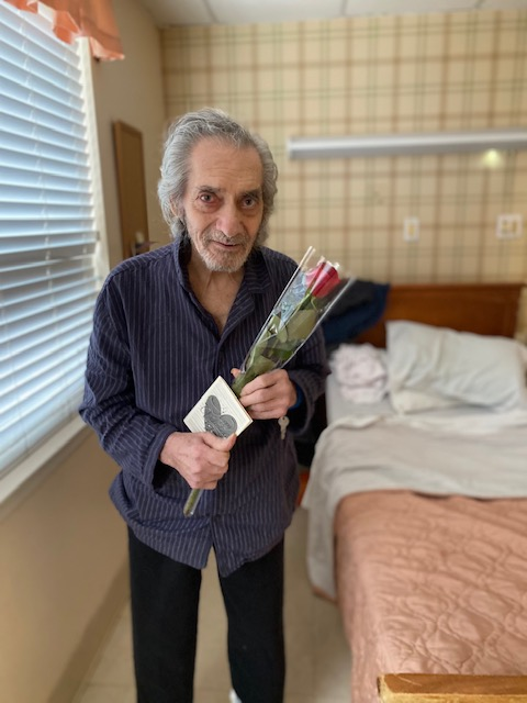 man standing holding rose and card