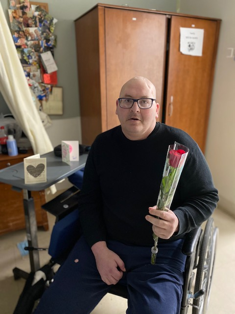 man in wheelchair holding rose