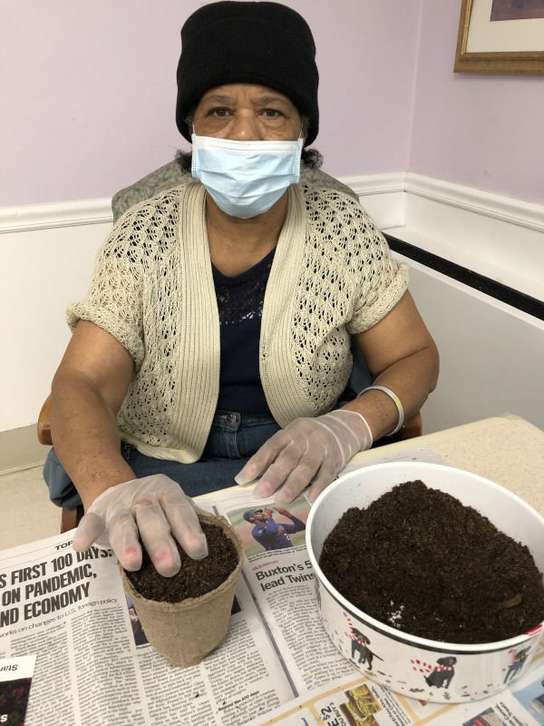 Woman looks up as she is planting seeds in planter