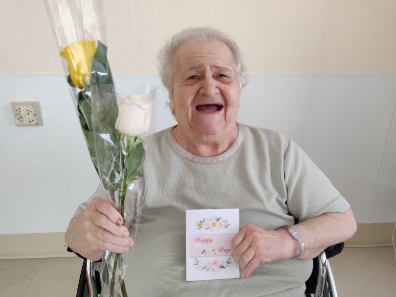 Woman smiling while holding flowers and card