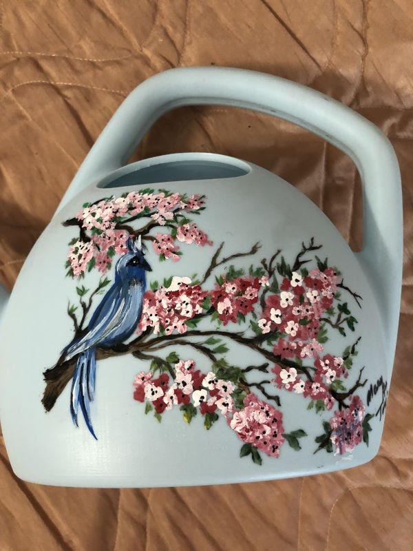 Painting of bird and flowers on watering can