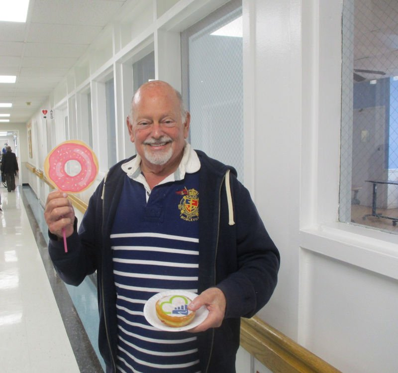Man holding donut on plate and donut sign
