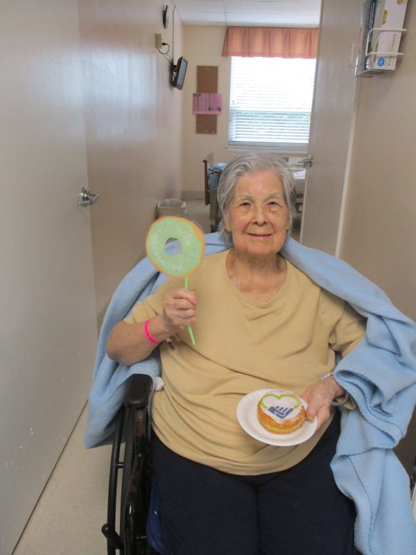 Woman in wheelchair holding donut and donut sign