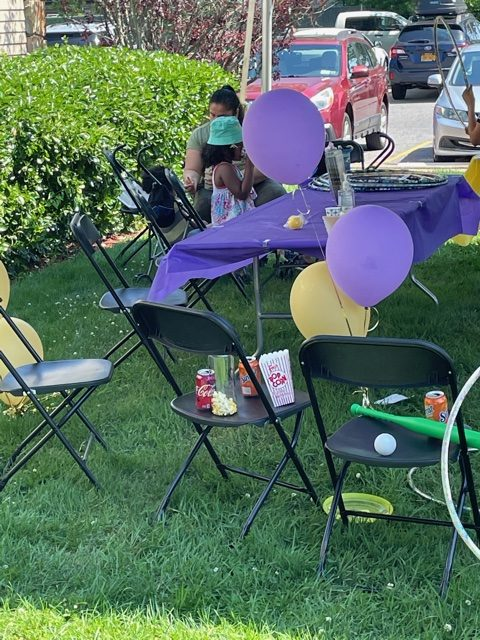 Table and purple and yellow balloons at the 2021 Community Event