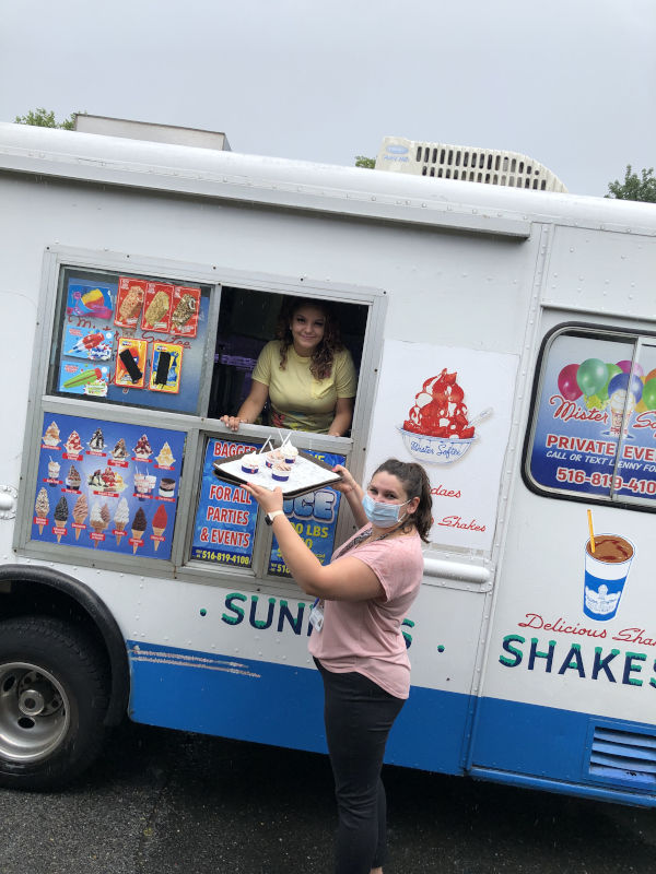 Woman holding tray of ice cream in front of ice cream truck