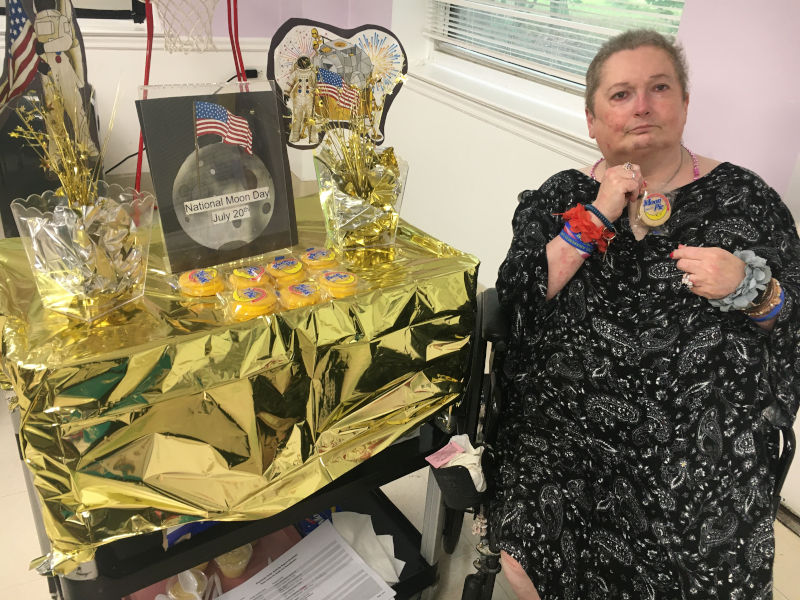Woman holding Moon Pie next to National Moon Day table