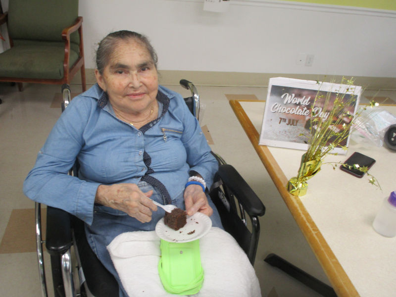 Woman in wheelchair eating chocolate cake