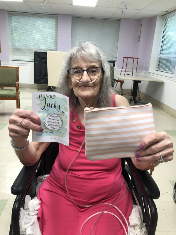 Woman holding up her lottery ticket and prize