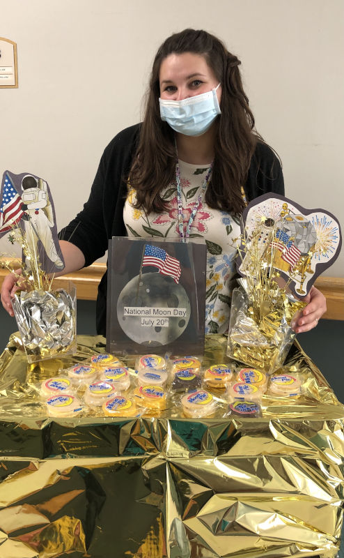 Employee standing behind National Moon Day table